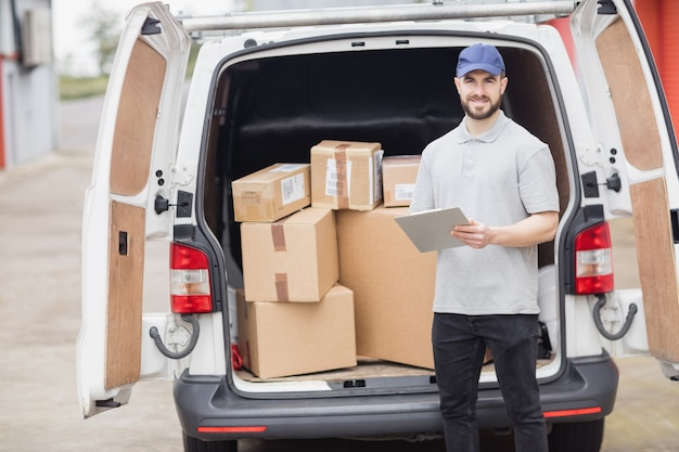 Entregador, segurando a área de transferência na frente de sua van