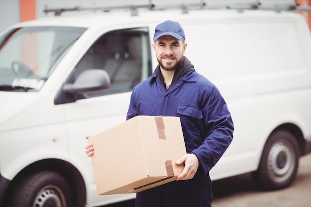 Entregador, segurando a caixa na frente de sua van