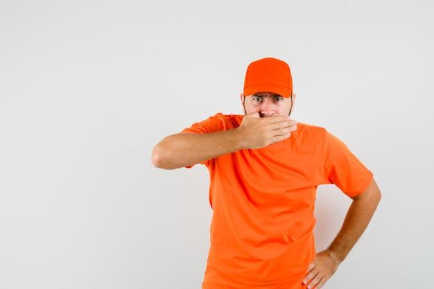 Entregador, segurando a mão na boca em camiseta laranja, boné e olhando sério, vista frontal.