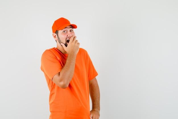 Entregador, segurando a mão na boca em t-shirt laranja, boné e olhando feliz, vista frontal.