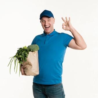 Entregador, segurando a sacola de compras e fazendo sinal de ok