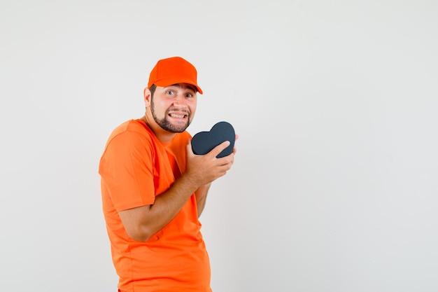 Entregador segurando caixa de presente em t-shirt laranja, boné e olhando feliz, vista frontal.