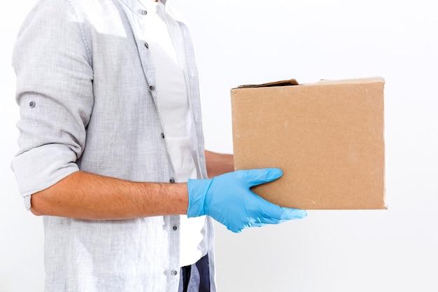 Entregador segurando caixas de papelão com máscara e luvas médicas de borracha. copie o espaço. transporte de entrega rápido e gratuito. compras online e entrega expressa. quarentena