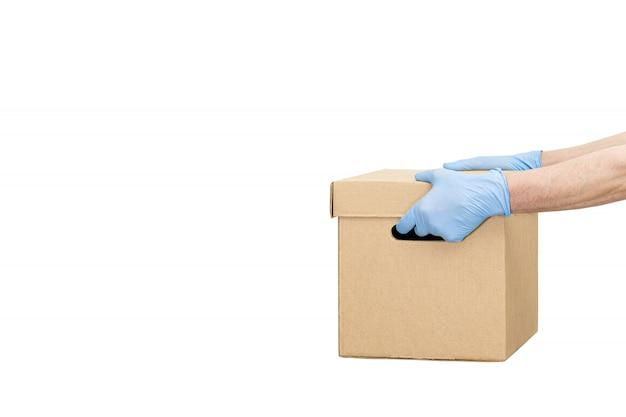 Entregador segurando caixas de papelão em luvas de borracha isoladas sobre o branco