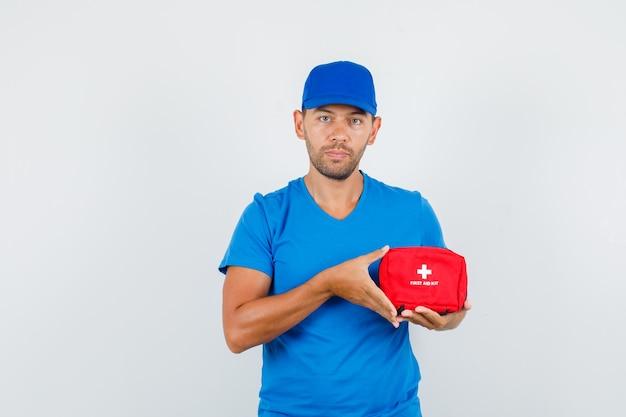 Entregador segurando kit de primeiros socorros em camiseta azul