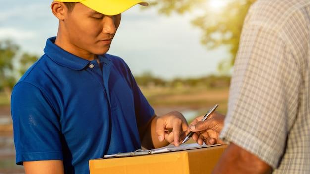 Entregador segurando marrom parcela ou entrega de caixas de papelão ao cliente no campo