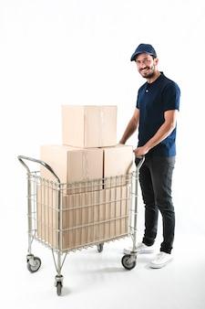 Entregador, segurando o carrinho com caixas de papelão
