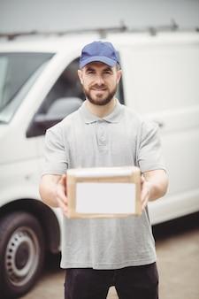 Entregador, segurando o pacote na frente de sua van
