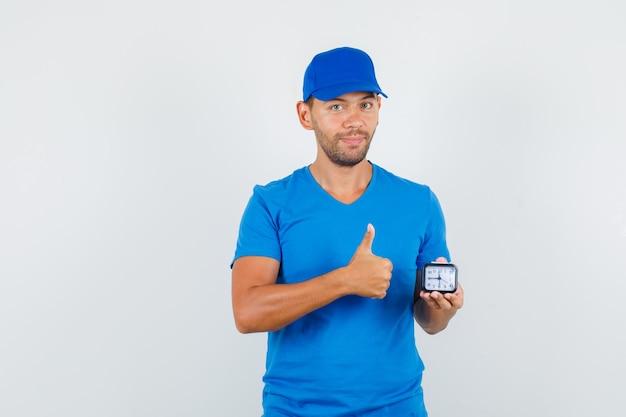 Entregador segurando o relógio com o polegar para cima em uma camiseta azul