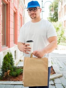 Entregador, segurando o saco e a xícara de café