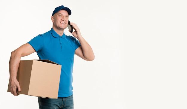 Entregador, segurando o smartphone e caixa de papelão
