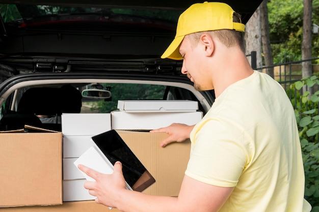 Entregador, segurando o tablet e caixa
