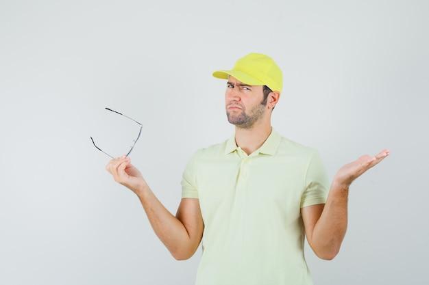 Entregador segurando óculos em uniforme amarelo e parecendo confuso. vista frontal.