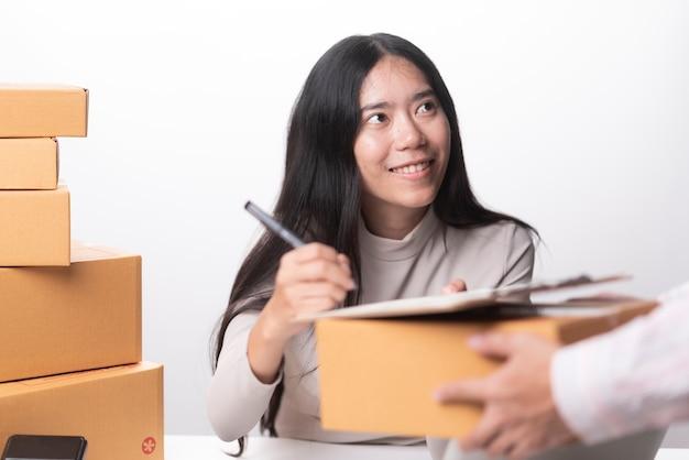 Entregador segurando pacote enquanto mulher está assinando documentos