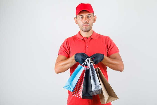 Entregador segurando sacolas de papel em uniforme vermelho, vista frontal de luvas.