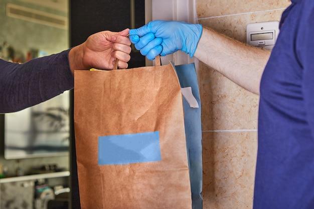 Entregador segurando sacos de papel em luvas médicas de borracha. quarentena. coronavírus. copie o espaço. entrega de transporte rápido e gratuito. loja online e entrega expressa.