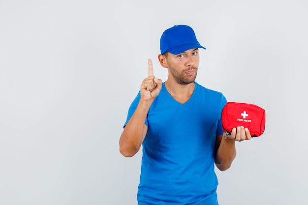 Entregador segurando um kit de primeiros socorros com o dedo para cima em uma camiseta azul