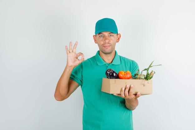 Entregador segurando uma caixa de vegetais com sinal de ok, camiseta verde e boné