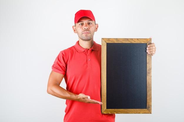 Entregador segurando uma lousa em vista frontal uniforme vermelha.