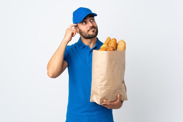 Entregador segurando uma sacola cheia de pães isolado no fundo branco, tendo dúvidas e com expressão facial confusa