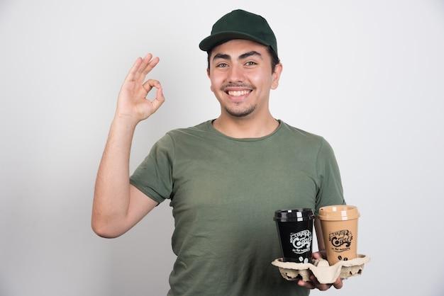 Entregador segurando xícaras de café para viagem em fundo branco.