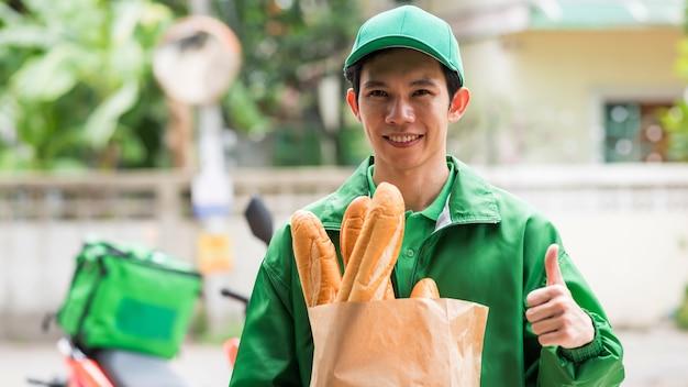 Entregador sorridente com o polegar para cima e segurando pão baguete para entregar ao cliente perto de motocicleta