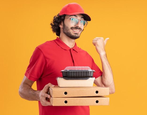 Entregador sorridente com uniforme vermelho e boné de óculos segurando pacotes de pizza com pacote de comida de papel e recipiente de comida olhando para frente apontando para o lado
