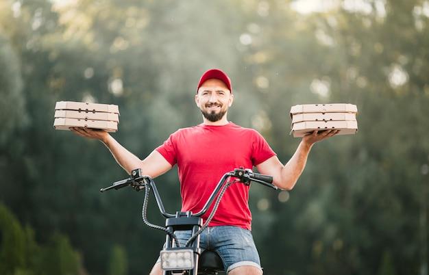 Entregador sorridente de baixo ângulo segurando caixas de pizza
