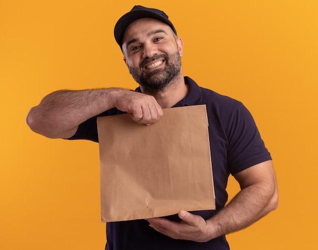 Entregador sorridente de meia-idade de uniforme e boné segurando um pacote de comida de papel isolado na parede amarela