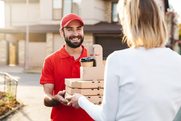 Entregador sorridente de uniforme vermelho dando pedido de comida para uma mulher caucasiana na rua