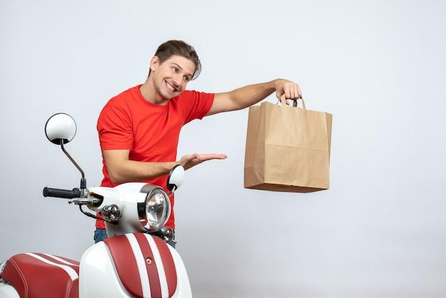 Entregador sorridente de uniforme vermelho em pé perto de scooter apontando a caixa de papel no fundo branco