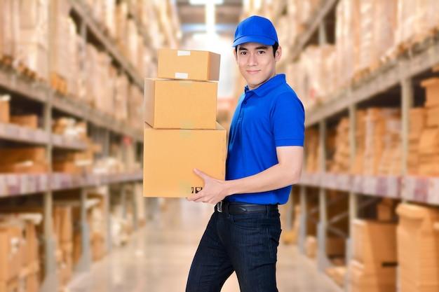 Entregador sorridente que transporta caixas no fundo do armazém em borrão