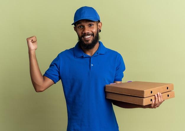 Entregador sorridente segurando caixas de pizza e apontando para trás, isolado na parede verde oliva com espaço de cópia