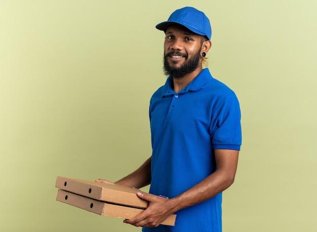 Entregador sorridente segurando caixas de pizza isoladas na parede verde oliva com espaço de cópia