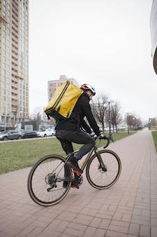 Entregador usando capacete e mochila térmica, andando de bicicleta enquanto trabalha