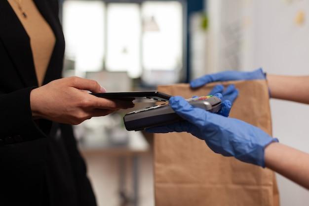 Entregador usando luvas de proteção recebendo pagamento de uma mulher de negócios usando smartphone nfc