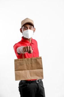 Entregador usando máscara médica e segurar a caixa nas mãos. entregador. conceito de entrega segura.