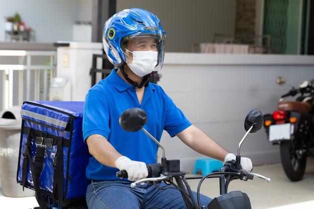 Entregador usando uniforme azul andando de motocicleta e caixa de entrega