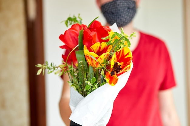 Entregador, vestindo uma máscara facial e entregando um buquê de flores
