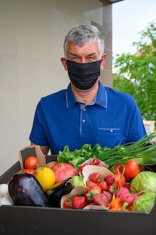Entregador, vestindo uma máscara facial e segurando uma caixa com legumes Foto gratuita