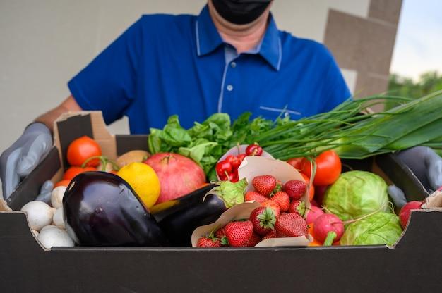 Entregador, vestindo uma máscara facial e segurando uma caixa com legumes