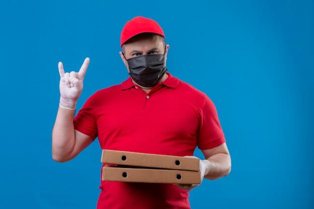 Entregador vestindo uniforme vermelho e boné com máscara protetora facial segurando caixas de pizza, fazendo o símbolo do rock com uma cara séria de pé sobre o espaço azul