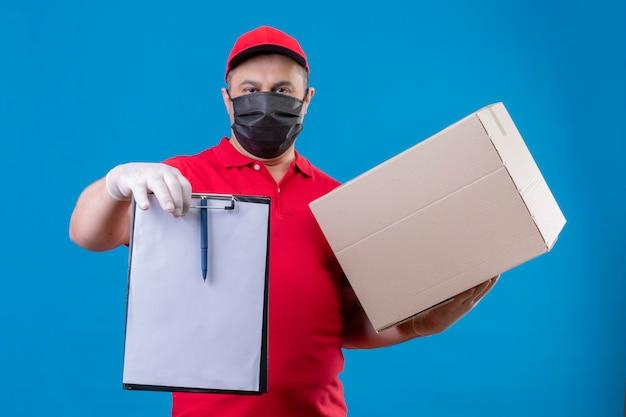 Entregador, vestindo uniforme vermelho e boné na máscara protetora facial, segurando a área de transferência e caixa de papelão com cara séria sobre parede azul