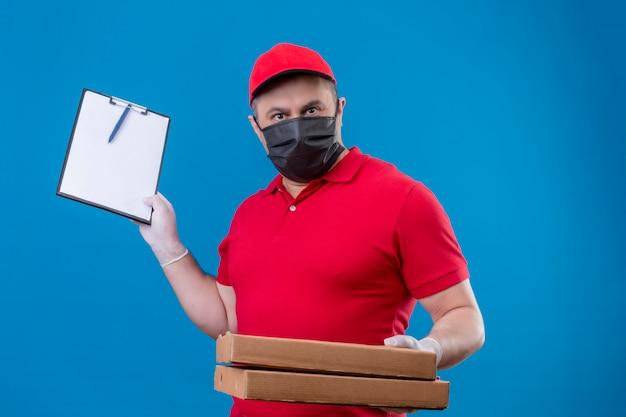 Entregador vestindo uniforme vermelho e boné na máscara protetora facial segurando caixas de pizza e prancheta com cara séria sobre parede azul