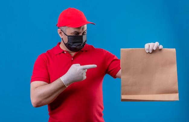Entregador vestindo uniforme vermelho e boné na máscara protetora facial segurando o pacote de papel apontando com o dedo indicador para ele sorrindo sobre parede azul isolada