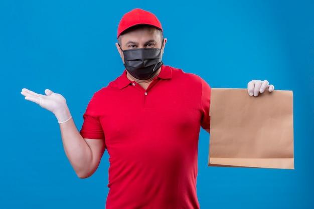 Entregador, vestindo uniforme vermelho e boné na máscara protetora facial, segurando o pacote de papel, apresentando-se com o braço oh, entregue a parede azul