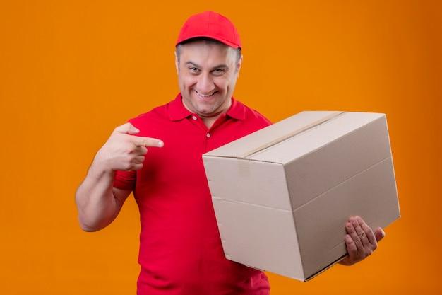 Entregador vestindo uniforme vermelho e boné segurando a caixa de papelão grande apontando com o dedo indicador para ele sorrindo confiante sobre parede laranja