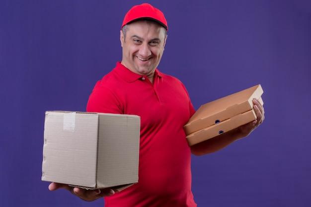 Entregador vestindo uniforme vermelho e boné segurando caixas de papelão sorrindo amigavelmente com uma cara feliz em pé