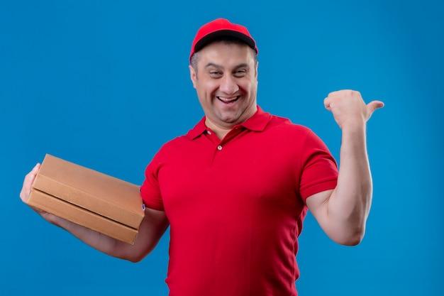 Entregador vestindo uniforme vermelho e boné segurando caixas de pizza sorrindo com o rosto feliz levantando o punho após uma vitória em pé sobre o espaço azul isolado