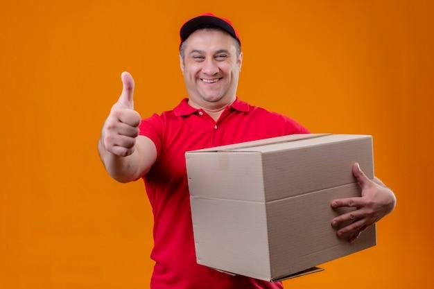 Entregador vestindo uniforme vermelho e boné segurando o pacote de papel saiu e feliz erguendo o punho após uma vitória de pé sobre o espaço azul isolado segurando o pacote da caixa olhando para veio